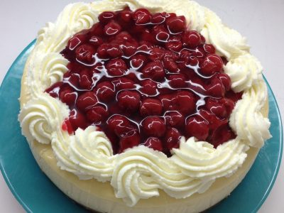Original Cheesecake with  a graham cracker crust. Topped with fresh cherry sauce and whipped cream.